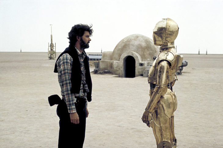 George Lucas, with actor Anthony Daniels, in costume as C3PO on the set of Star Wars, 1977. (PhotoFest)